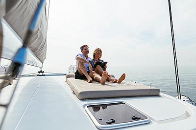 Couple sitting on deck of catamaran, relaxing, woman reading book - p300m2012485 von Bonninstudio