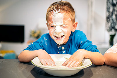 Smiling boy smearing face in flour and water at home - p300m2273599 by Albert Martínez