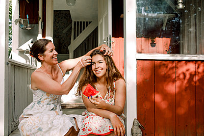 Smiling mother tying daughter's hair while sitting outdoors - p426m2227800 by Maskot