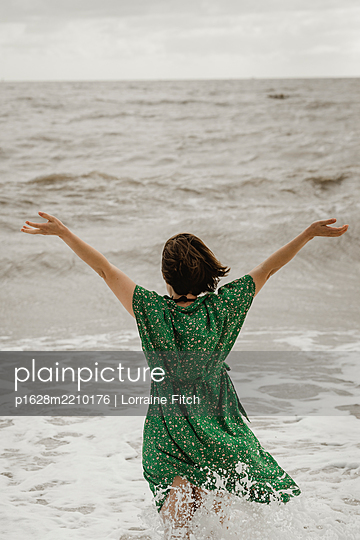 Woman stands in the sea with arms outstretched - p1628m2210176 by Lorraine Fitch