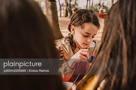 Cute girl decorating pine cone with sisters at park - p300m2225465 by Eloisa Ramos