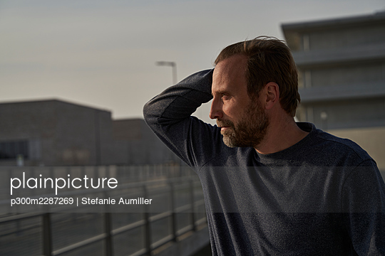 Mature businessman with hand in hair looking away - p300m2287269 by Stefanie Aumiller