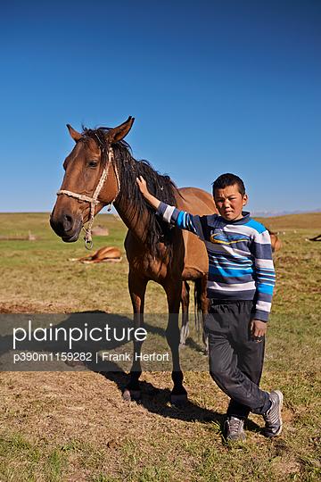 Indigener Junge mit Pferd in Zentralasien - p390m1159282 von Frank Herfort