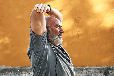An older man with white hair and beard is stretching his arm - p1166m2216947 by Cavan Images