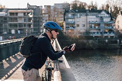 Senior man with cyclist helmet using smartphone on bridge - p300m1581257 von Gustafsson