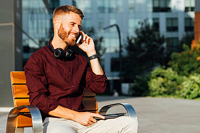 Businessman talking on mobile phone while sitting on bench during sunny day - p300m2250853 by Boy photography