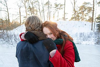 Boyfriend embracing girlfriend during winter - p300m2287645 by Frank van Delft