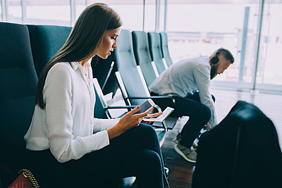 Young businesswoman holding smart phone and passport while sitting at waiting area in airport - p426m2074797 by Maskot
