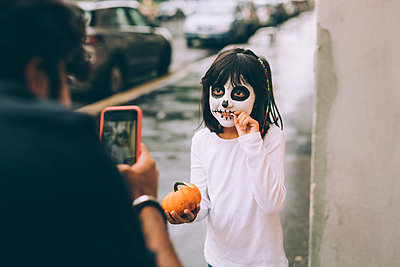 Father photographing daughter at Halloween - p429m2217749 by Eugenio Marongiu