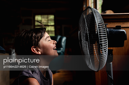 Young boy with eyes closed cooling off in front of a fan in dark room. - p1166m2214626 by Cavan Images