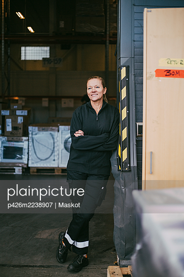 Smiling businesswoman with arms crossed looking away while leaning on wall at warehouse - p426m2238907 by Maskot