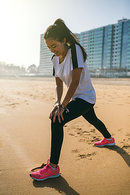 Spain, Gijon, young woman stretching on the beach - p300m1188371 by Marco Govel