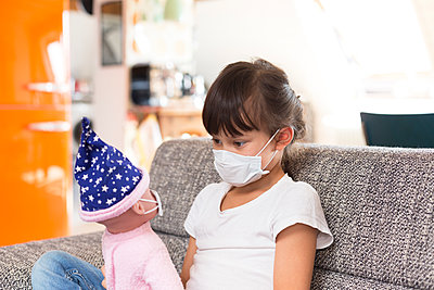 Little girl with protective mask sitting on couch at home playing with doll - p300m2180157 by Stefan Rupp