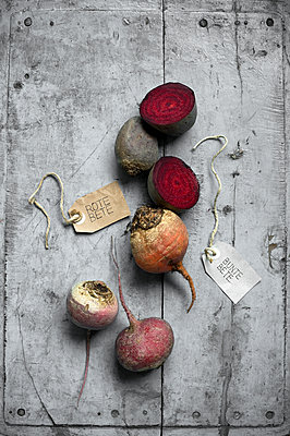 Beets and labels lying on gray wooden surface - p300m2264641 by Achim Sass