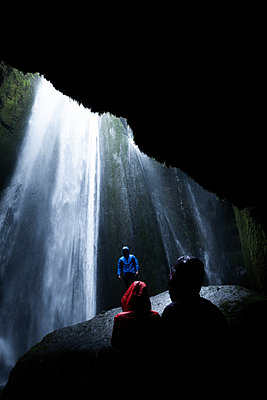 Tourists below overhanging rock in front of waterfall, Selfoss, Arnessysla, Iceland - p429m2135686 by Alex Eggermont