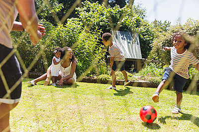 Happy family playing soccer in sunny summer backyard - p1023m2212721 by Tom Merton