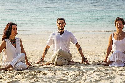 Thailand, Koh Phangan, three people doing yoga on a beach - p300m1568324 by Mosuno Media