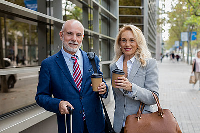 Portrait of smiling senior businessman and businesswoman with baggage on the go in the city - p300m2070359 von Mauro Grigollo