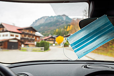 Protective mask hanging on rear-view mirror of car - p300m2253216 by Annika List