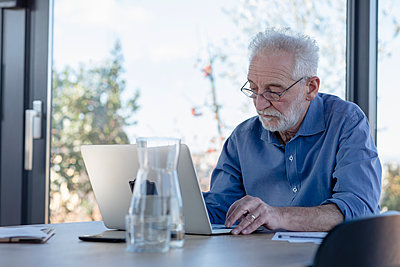 Senior man working on laptop while sitting at home - p300m2265108 by Emma Innocenti