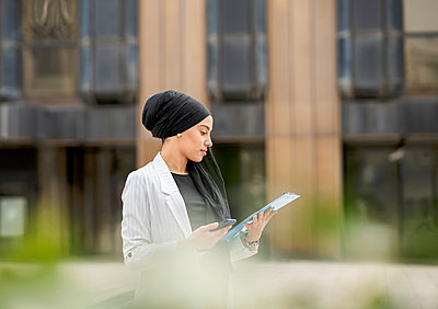 Young businesswoman wearing headscarf planning strategy while standing outdoors - p300m2266383 by Jose Carlos Ichiro