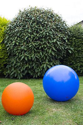 Bad Laer, ein blauer und ein oranger Ball (Sitzball und Huepfball) liegen auf dem gruenen Rasen im Garten eines Einfamilienhauses - p627m1035272 von Hendrik Rauch