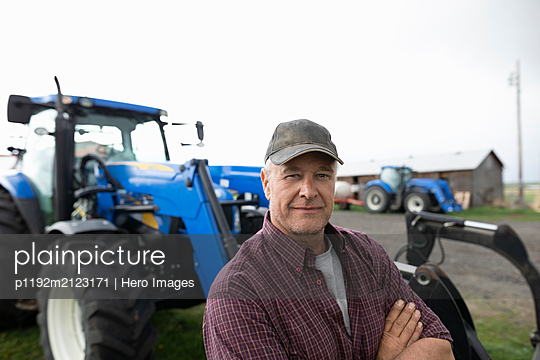 Portrait confident male farmer standing in front of tractor - p1192m2123171 by Hero Images