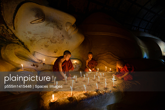 Asian monks lighting candles in temple