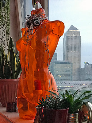 Plastic torso with headphones and Canary Wharf Tower - p1048m2016784 by Mark Wagner