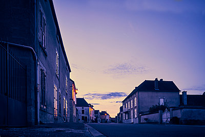 Village road and residential houses at twilight - p1312m2269989 by Axel Killian