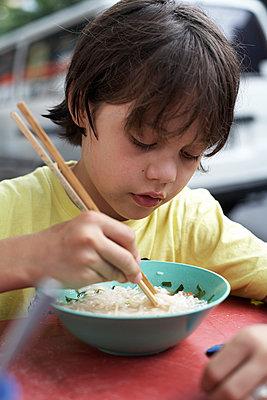Junge isst Nudelsuppe mit Stäbchen, Bangkok, Thailand - p1316m1160483 von Enno Kapitza