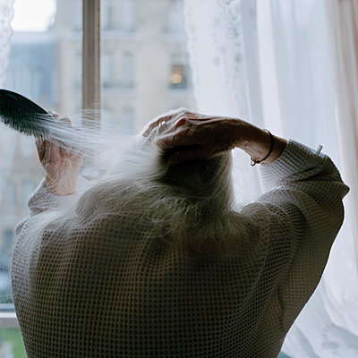 Elderly woman combs her hair - p1468m1528575 by Philippe Leroux