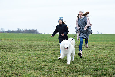 Two laughing girls running on a meadow with dog having fung - p300m2079289 von Eyecatcher.pro