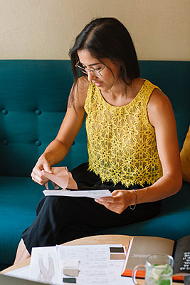 Fashion designer sitting on couch checking color samples - p300m2140111 by Alberto Bogo