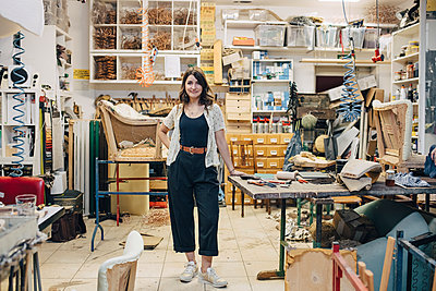 Portrait of confident female upholstery worker standing in workshop - p426m2045905 by Maskot