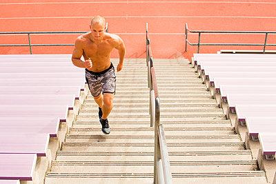 Caucasian man running on staircase on bleachers - p555m1304599 by Adam Hester