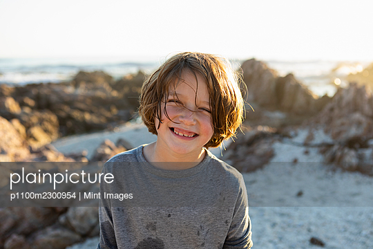 A young boy on the beach at sunset among the rocks of De Kelders. - p1100m2300954 by Mint Images