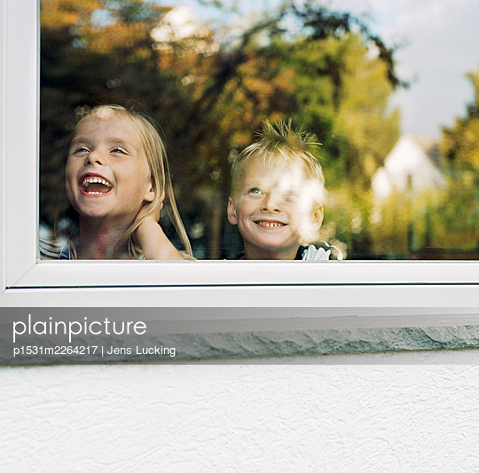 Twin Brother And Sister Looking Out Of Window, Laughing And Smiling - p1531m2264217 by Jens Lucking