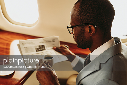 Businessman reading newspaper while traveling in airplane - p300m2257058 by OneInchPunch