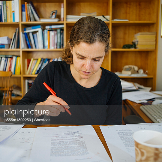 Teacher grading papers at messy office desk