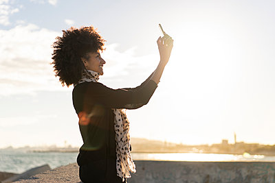 Smiling woman taking selfie with smartphone near the sea - p300m2068327 von VITTA GALLERY