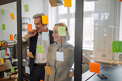 Happy colleagues looking at sticky notes at glass pane in office - p300m2143785 by Gustafsson