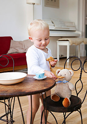 Boy toddler at tea party with his teddy - p4297397f by Fiona Jackson-Downes and Dirk Lindner