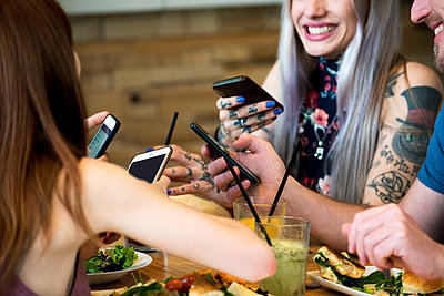 Friends all using smart phones - p623m1506840 by Eric Audras