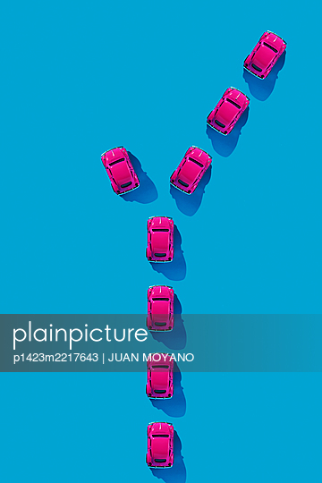Line of pink toy cars and a divergent toy car on a blue background - p1423m2217643 von JUAN MOYANO