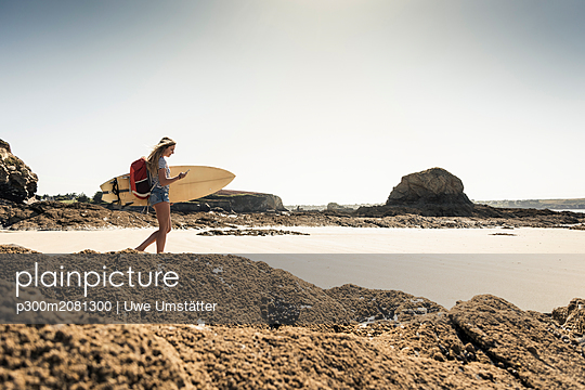 Young woman on the beach, carrying surfboard, using smartphone - p300m2081300 by Uwe Umstätter