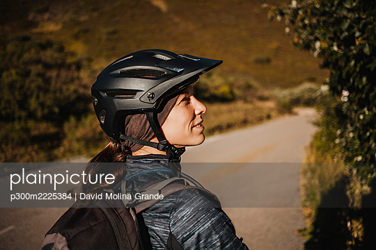 Woman wearing cycling helmet standing on mountain path at Somiedo Natural Park, Spain - p300m2225384 by David Molina Grande