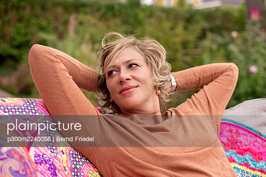 Smiling woman sitting with hands behind head on sofa at back yard - p300m2240056 by Bernd Friedel