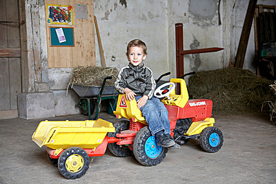 Boy on a toy tractor - p1230m1042621 by tommenz