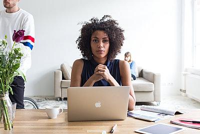 Attraktive Geschäftsfrau mit Afro am Laptop in einem modernen Büro mit jungem Mann auf einem Fahrrad und einer Frau auf Sofa im Hintergrund - p1301m2020286 von Delia Baum